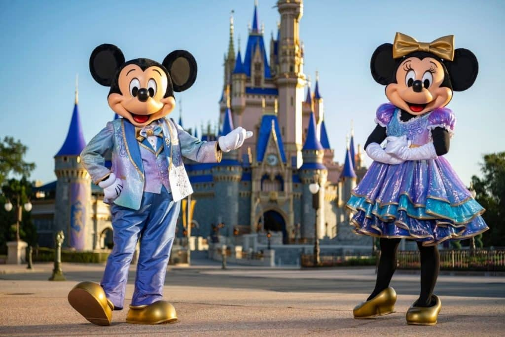 Photo of Mickey and Minnie Mouse in their EARidescent costumes, posing in front of Cinderella's Castle at Disney World's Magic Kingdom.