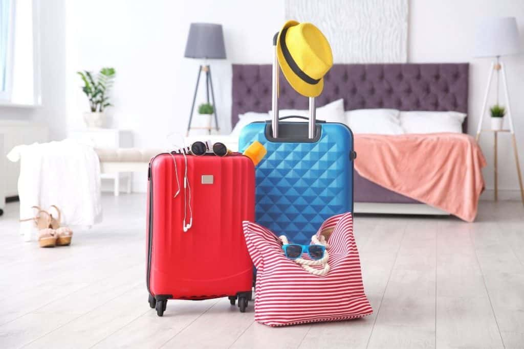 Photo of 2 roller suitcases and a tote bag propped up in a bedroom ready to go
