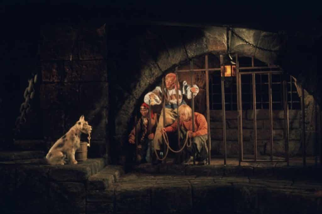 Photo of a scene in Pirates of the Caribbean with 3 pirates in a jail trying to get keys from a dog holding them in his mouth.