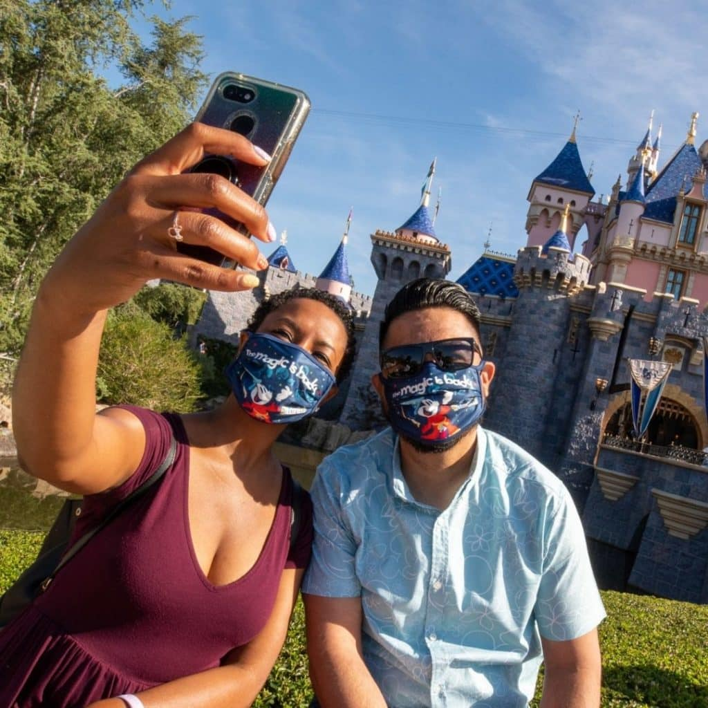Photo of a couple taking an Instagram photo in front of Sleeping Beauty's castle at Disneyland in California.
