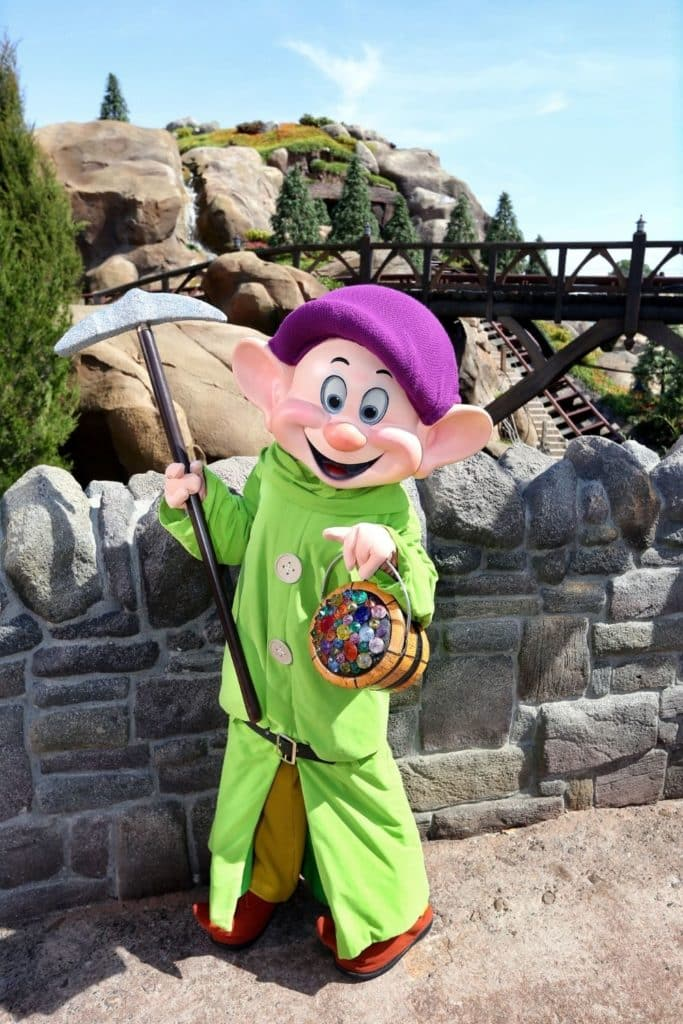 Photo of Dopey holding a hoe and bucket full of jewels outside the Seven Dwarfs Mine Train roller coaster at Magic Kingdom.