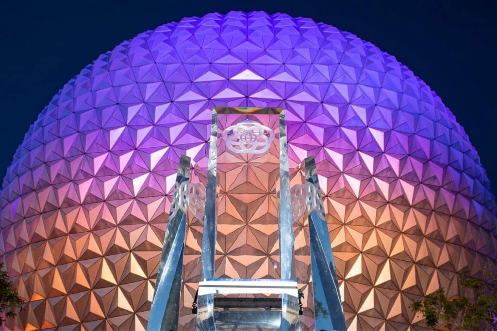 Closeup of the Spaceship Earth Epcot ball at night, light up with purple to orange lights.