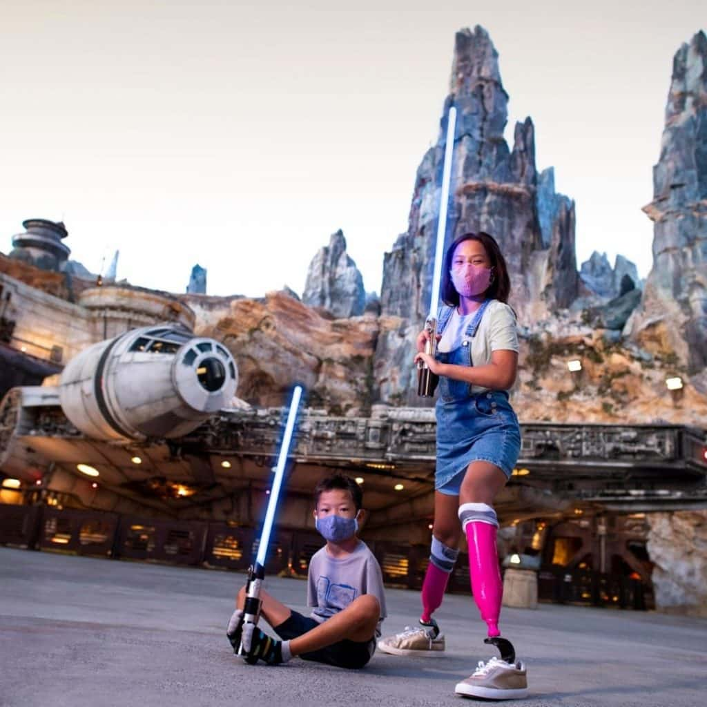 A woman and a young boy pose with lightsabers in front of Star Wars: Galaxy's Edge at Disneyland's California Adventure theme park.