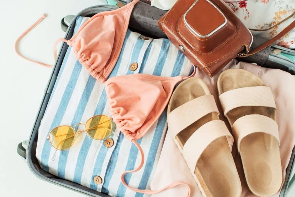 Closeup of a suitcase with clothing, a swimsuit, sandals, sunglasses, and a camera sitting inside.