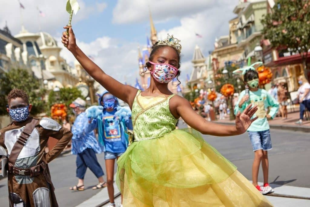 Photo of a girl dressed in a Tiana costume with kids behind her also dressed in Disney costumes for the Boo Bash, which takes place at Disney World in September, October, and August.