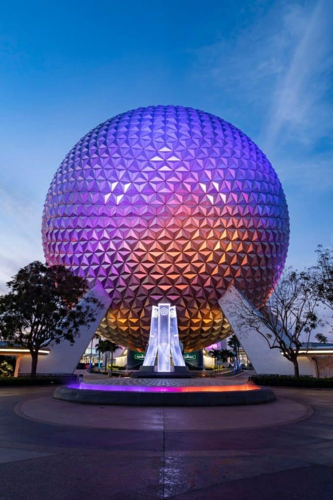 Photo of the Epcot ball light up in purple, blue, and orange.