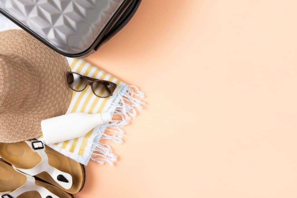Top-down photo of sandals, beach blanket, sunglasses, and a sun hat next to a suitcase.